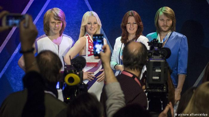 Wax figures of the band members of ABBA at the museum in Stockholm with a crowd taking pictures of them (picture alliance/dpa)