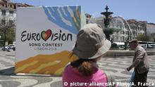 People walk past a banner advertising the Eurovision Song Contest Friday, May 4 2018, in Lisbon's Rossio Square. The Eurovision final will be held in Lisbon May 12. (AP Photo/Armando Franca) |