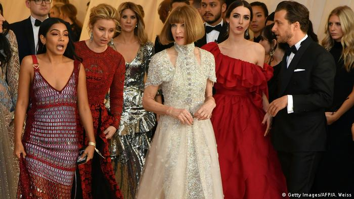 Anna Wintour in a beaded white gown surruonded by young women (Getty Images/AFP/A. Weiss)