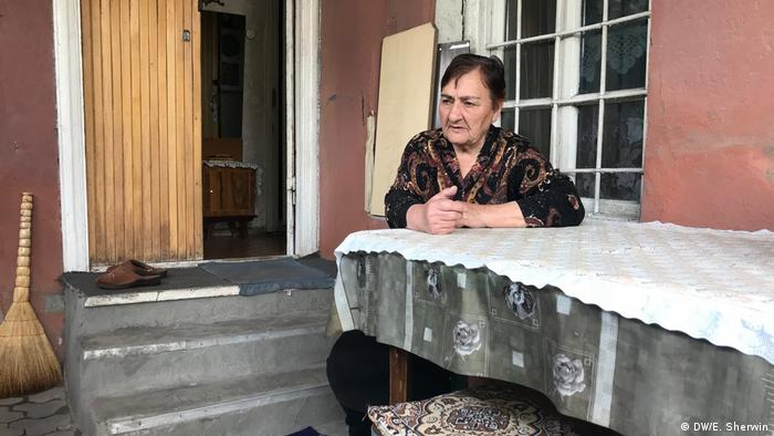 Clara Melkumyan sits at a table outside her house in Yerevan.