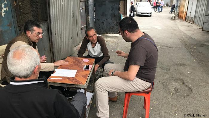 Local residents on Yerevan's Firdaus market play cards.