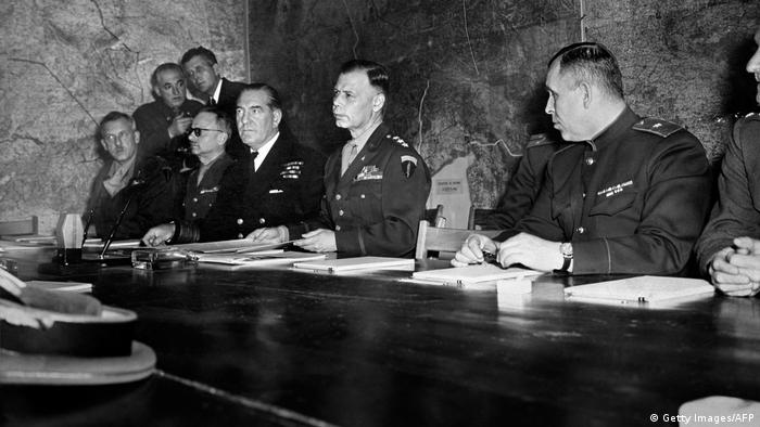 Allied officers sign the German surrender document at the Allied headquarters in Reims,