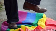 Hass gegen Schwule Mann trampelt auf einer LGBT Flagge herum