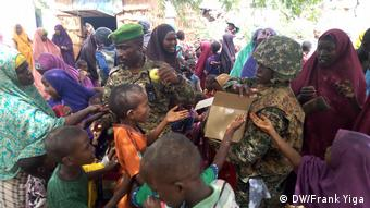 soldiers holding boxes handing food to people (DW/Frank Yiga)