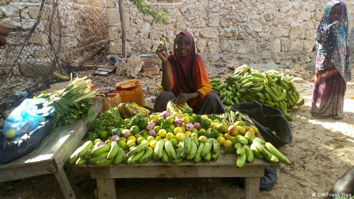woman seated, selling bananas and other produce