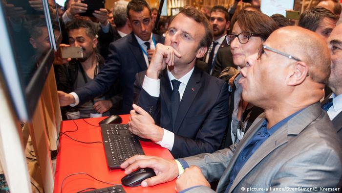 Macron looks at a computer screen while someone explains something to him at the Frankfurt Book Fair (picture-alliance/SvenSimon/E. Kremser)