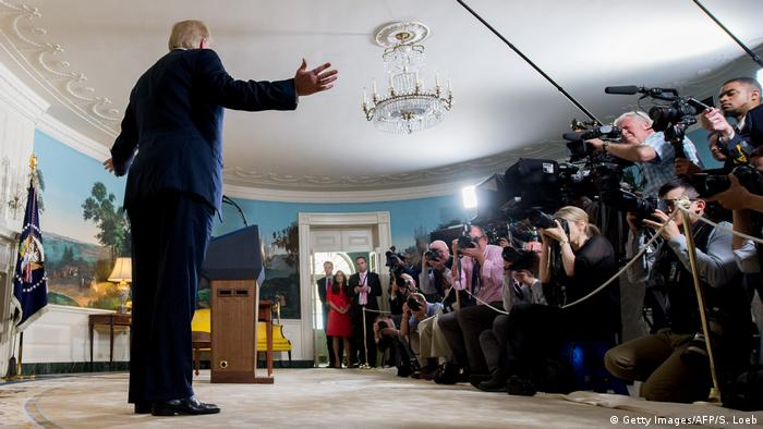 Trump makes an announcement to a room full of journalists