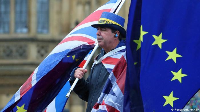 A man draped in a British flag carries another large British flag in one hand and an EU flag in the other.