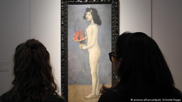 Women looking at Picasso's Woman holding a flower basket painting