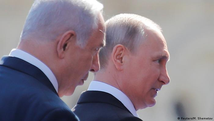 Netanyahu stands beside Vladimir Putin