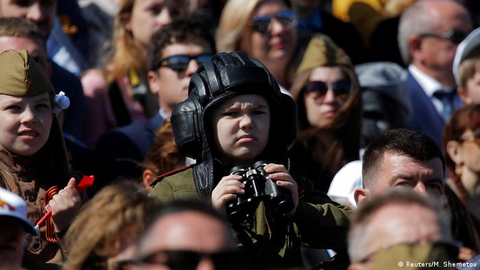A boy holds binoculars while squinting to see the parade (Reuters/M. Shemetov)