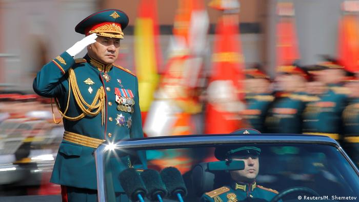 Russia's Sergei Shoigu salutes while riding in an open limo (Reuters/M. Shemetov)