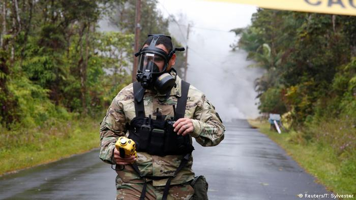 Lieutenant Aaron Hew Lew, of the Hawaii National Guard, measures levels of toxic gas near a lava flow in the Leilani Estates subdivision