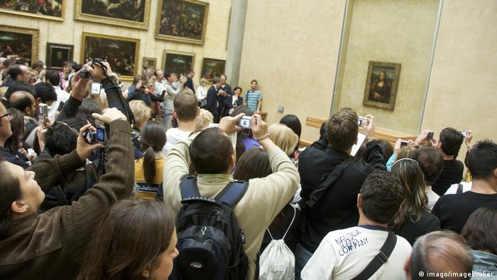 Gente mirando y fotografiando la Mona Lisa.