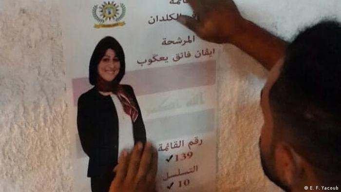 A man hanging up an election poster of Evan Faek Yacoub