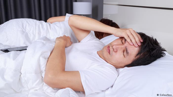 Two people in bed, one appears to be sleeping, the other, a man, is holding his head as though he has a headache and can't sleep