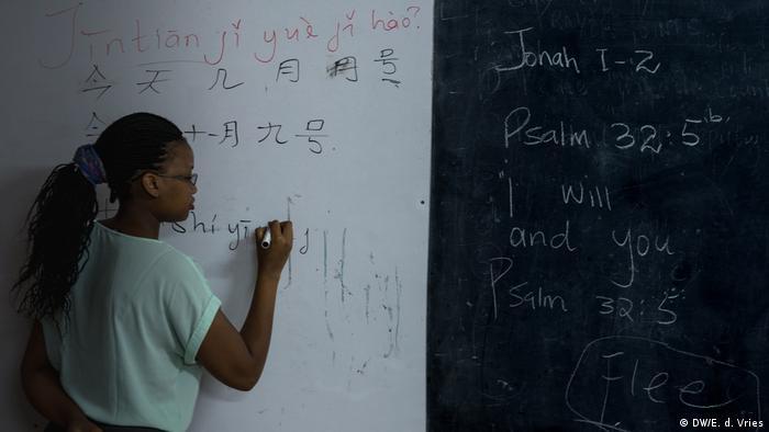 A teacher writes on a board in a classroom (DW/E. d. Vries)
