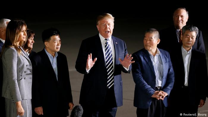 Trump gestures as he speaks while standing alongside released prisoners and melania Trump