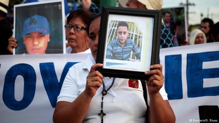 Protesters hold pictures of victims killed in a government crackdown