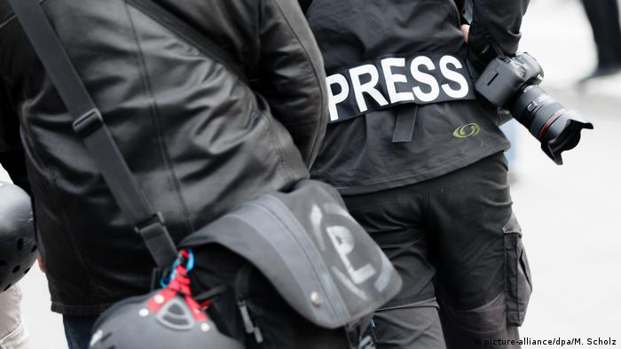 Journalists, one with Press written on his jacket