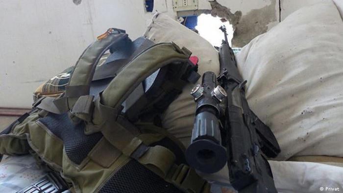 A rifle and backpack propped up against a wall