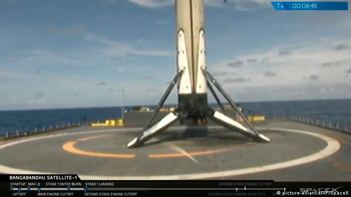 A SpaceX Falcon 9 reusable booster rockets lands on a drone ship in the Atlantic Ocean