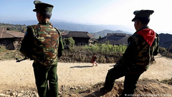 Two members of the insurgent group, the Ta-ang National Liberation Army (TNLA), stand guard in a village in the northern Shan state in Myanmar.