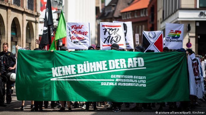 Anti-AfD protesters parade a green banner through Münster