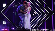 A man takes the microphone from Britain's singer Susanna Marie Cork aka SuRie as she performs Storm during the final of the 63rd edition of the Eurovision Song Contest 2018 at the Altice Arena in Lisbon, on May 12, 2018. (Photo by Francisco LEONG / AFP) (Photo credit should read FRANCISCO LEONG/AFP/Getty Images)
