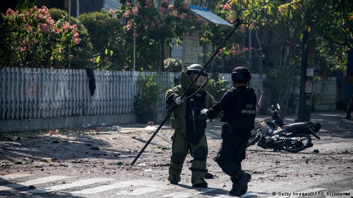 Indonesian bomb squad members examine the site of a suicide bombing outside a church in Surabaya
