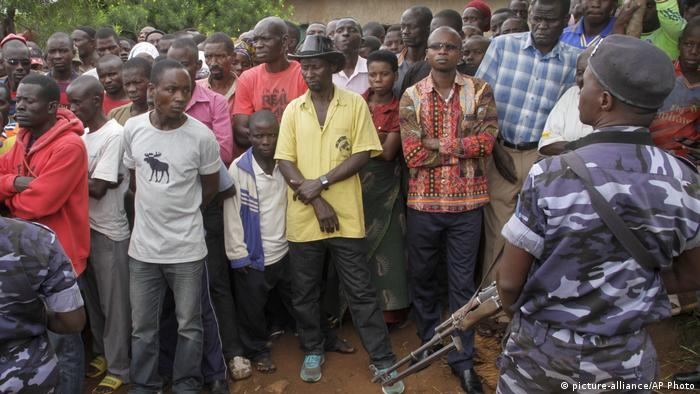 A crowd of Burundians and a soldier stand on the spot where an attack took place in early May