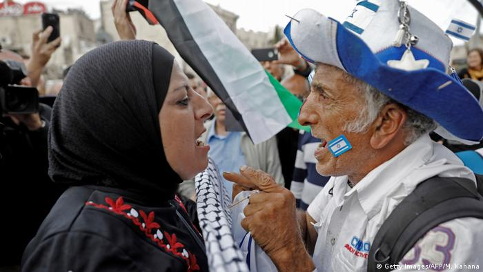 A man displaying an Israeli flag confronts a Palestinian woman holding a keffiyeh
