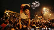Supporters hold a banner with the picture of Muqtada al-Sadr in a spontaneous rally after preliminary results were anounced(picture alliance/AP/H. Mizban)