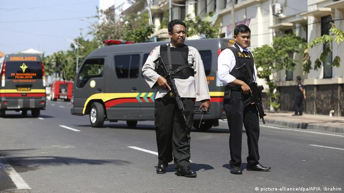 Two policemen stand guard after an explosion in Surabaya in Indonesia