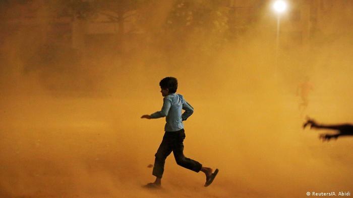 Boy running through dust storm in New Delhi
