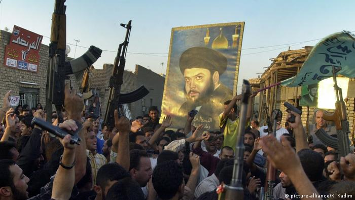 Supporters of radical Shiite cleric Muqtada al-Sadr shoot their guns in the air as they hoist a picture of al-Sadr to honour Majid Kassim who was killed in the fighting in Najaf, during a traditional celebration of fallen soldiers in the Shiite strong hold of Sadr city in Baghdad