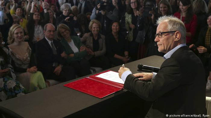 Thierry Fremaux signs a pact as audience members look on (picture-alliance/dpa/J. Ryan)