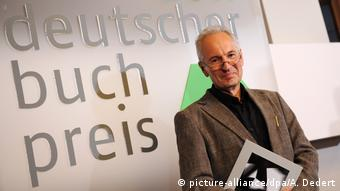 Eugen Ruge stands in front of a wall with the words German Book Prize