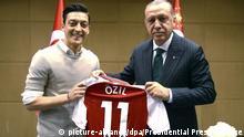 13.05.2018, Großbritannien, London. Recep Tayyip Erdogan, Staatspräsident der Türkei, hält zusammen mit Fußballspieler Mesut Özil vom englischen Premier League Verein FC Arsenal, ein Trikot von Özil. Der türkische Präsident Erdogan ist zu Besuch in London. (zu dpa-Meldung: «Foto mit Erdogan: Özil und Gündogan sorgen für Wirbel» vom 14.05.2018) Foto: Uncredited/Pool Presdential Press Service/AP/dpa +++(c) dpa - Bildfunk+++ |