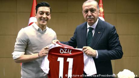 Özil pictured handing a football jersey to Erdogan (picture-alliance/dpa/Uncredited/Presdential Press Service)