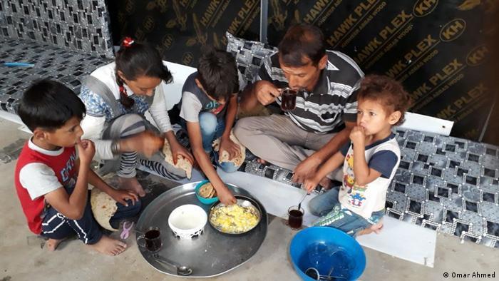 بعض البيض واللبن والشاي والخبز - عمر أحمد وأبناؤه يتناولون طعامهم في مخيم النازحين
