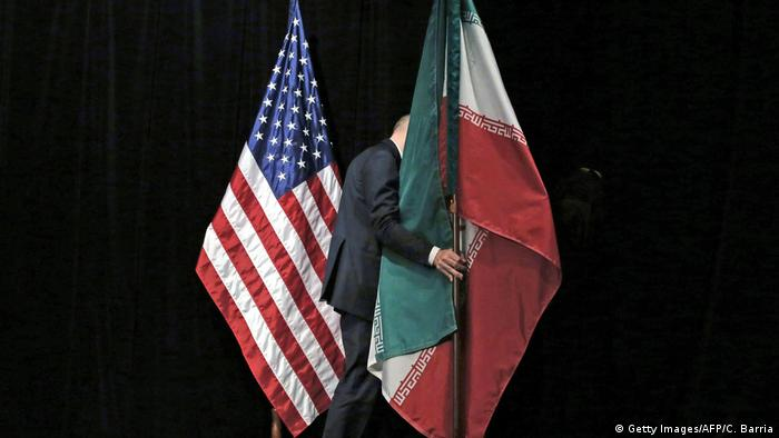 Seorang staf memindahkan bendera Iran