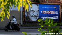 FILE PHOTO: A man rides his moped past a government billboard displaying George Soros in monochrome next to a message urging Hungarians to take part in a national consultation about what it calls a plan by the Hungarian-born financier to settle a million migrants in Europe per year, in Szolnok, Hungary, October 2, 2017. Picture taken October 2, 2017. REUTERS/Bernadett Szabo/File Photo