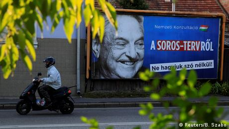 A man rides his moped past a government billboard displaying George Soros