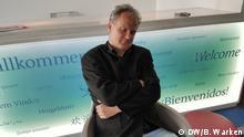 Symbolbild: Der Autor Leonhard Thoma sitzt vor einer Theke mit dem Gruß Willkommenin mehreren Sprachen in einem Sessel und hat den Kopf schlafend zur Seite geneigt.