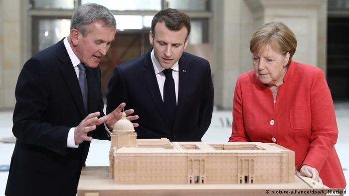 Neil MacGregor. Emmanuel Macron und Angela Merkel beugen sich über ein Modell des Berliner Schlosses