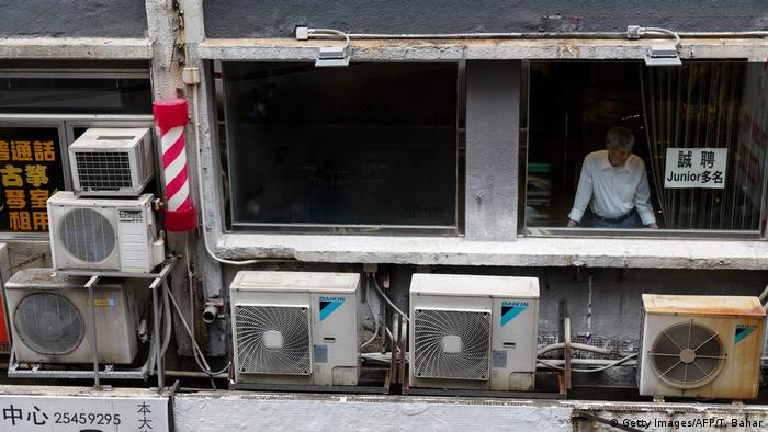Air conditioning units are seen as a man looks out of a window of a mixed business-residential building in Hong Kong's Central district