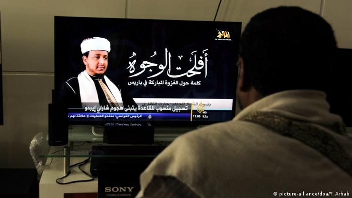 A Yemeni man watches new of TV showing a senior member of AQAP claim responsibility for the attack