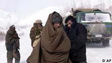 Afghans shiver under a heavy snow storm as they wait to cross the Salang Tunnel Thursday February 7, 2002 which was buried in the avalanche hundred more. Rescuers labored Thursday in intense cold high in the Hindu Kush mountains to save scores of people trapped in a snow avalanche. More than 190 people were rescued so far and the government appealed for help in reaching others stuck in the rugged mountain pass, 130 kilometers (80 miles) north of Kabul, Afghanistan. (AP Photo/Bullit Marquez)