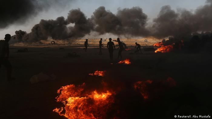 Fires burn as protesters gather in the background while smoke rises (Reuters/I. Abu Mustafa)